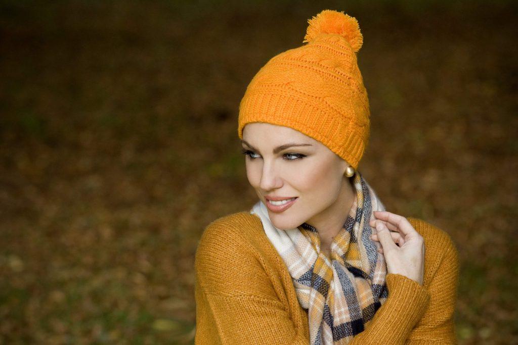 ... chemo beanie hat with Woman wearing a soft orange Single Rib Knit  beanie hat ... b298ecadba56
