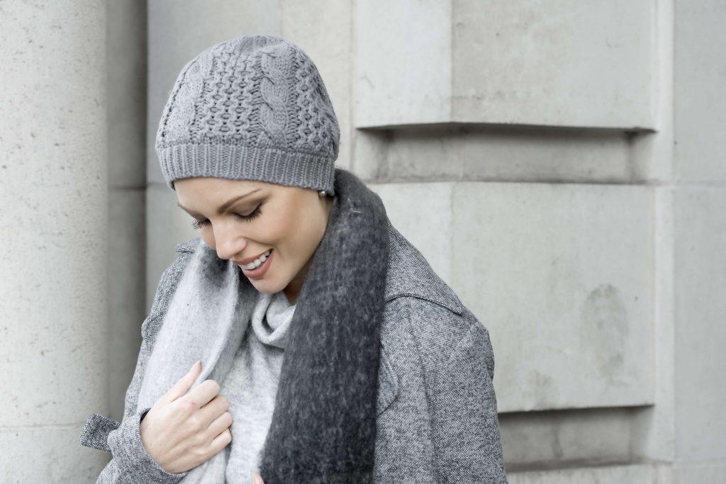 Woman wearing a soft grey knitted Basketweave Stitch hat