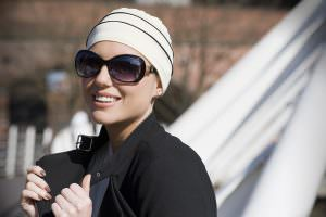 A woman wearing white chemo cap with black piping details