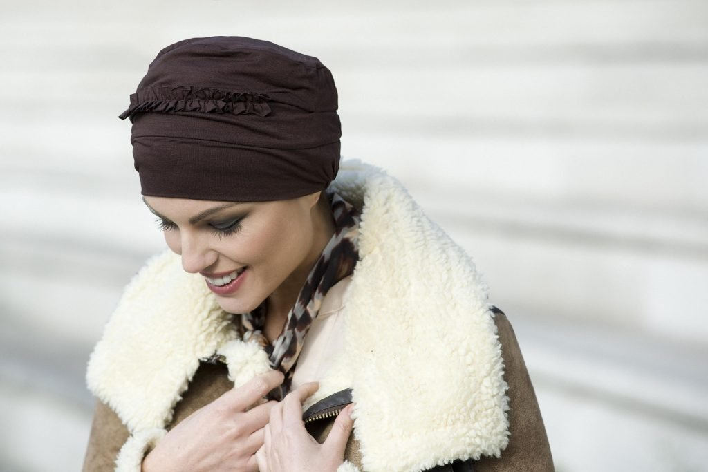 Woman wearing brown soft chemo cap with ruffled details at the front.