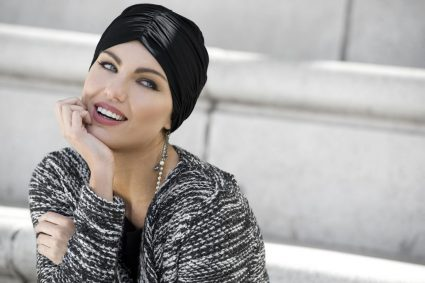 Hats for cancer patients - Rosalind Woman wearing black soft chemo cap with ruching details at the front and the sides