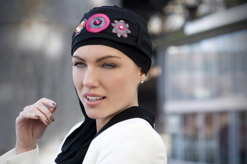 woman wearing black and pink chemotherapy headwear