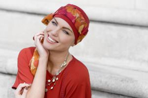 Woman wearing red floral chemo scarf