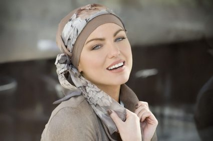 Woman wearing light brown floral headscarf which is one of our signature cancer scarves