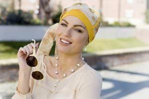 Woman wearing yellow sunflower chemo headwear