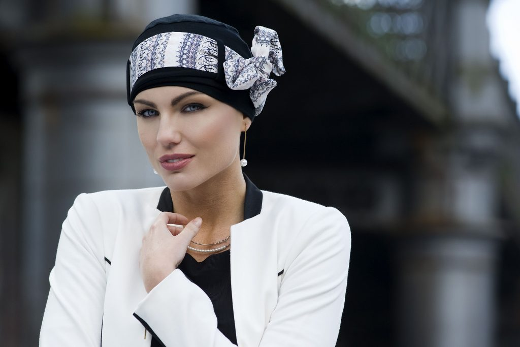 Woman wearing black chemo cap with white patterned head tie in a form of a bow