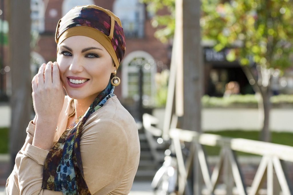 Woman wearing light brown floral chemo headwear