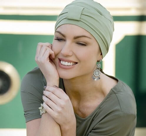 Woman wearing green bamboo chemo headwear