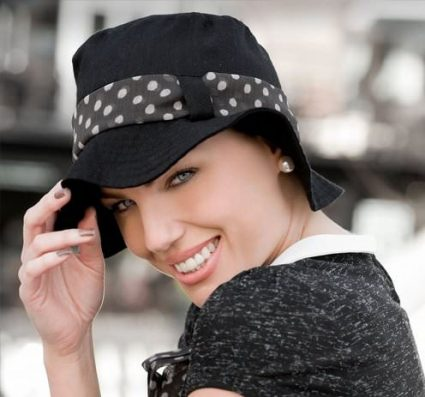 A woman wearing black sun hat with white polka dot head tie