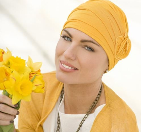 Woman wearing yellow embedded rose detail on soft chemo cap.