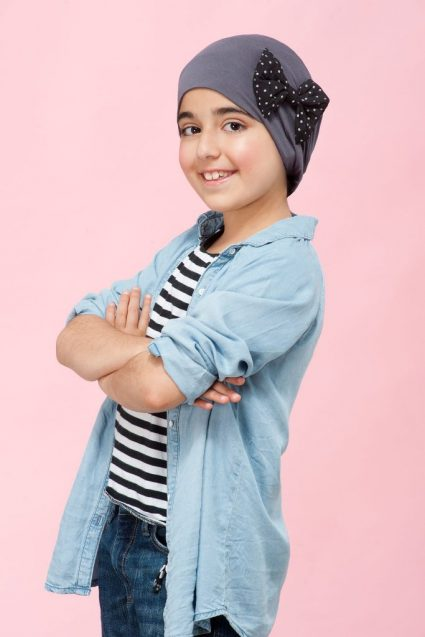 Girl wearing a grey headwear with polka dot side bow