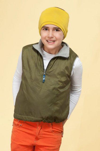 A boy wearing yellow chemo cap.