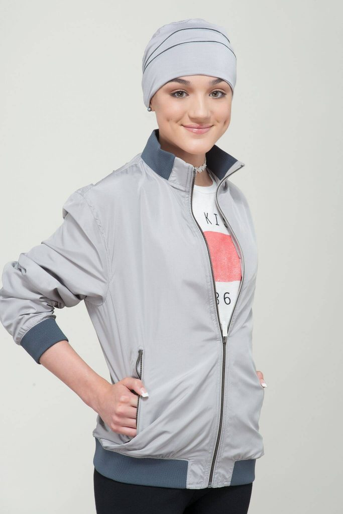 A teenage girl wearing grey with black piping headwear.