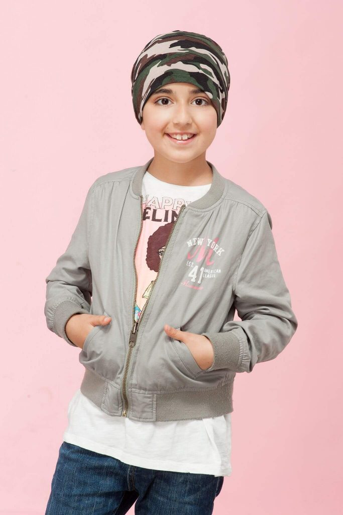 A girl wearing camo prints, layered chemo hat.