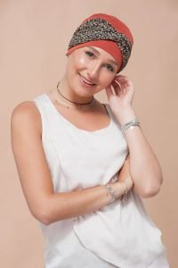 A teenage girl wearing orange chemo hat with golden flower head tie.