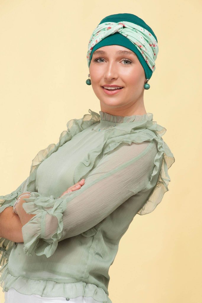 A teenage girl wearing forest green chemo hat with flower head tie.