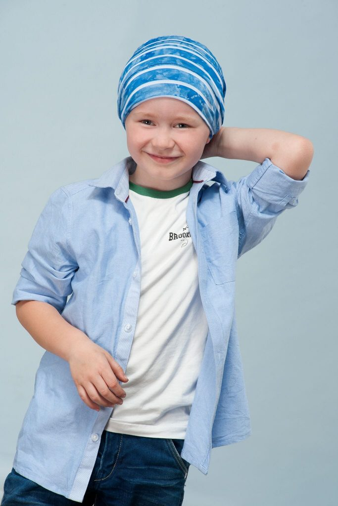 A boy wearing Turquoise Blue layered chemo hat