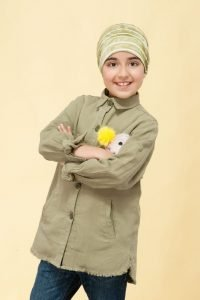 A girl wearing pale green layered chemo hat.