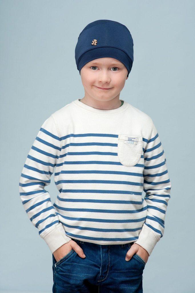 A boy wearing dark blue chemo cap with teddy button
