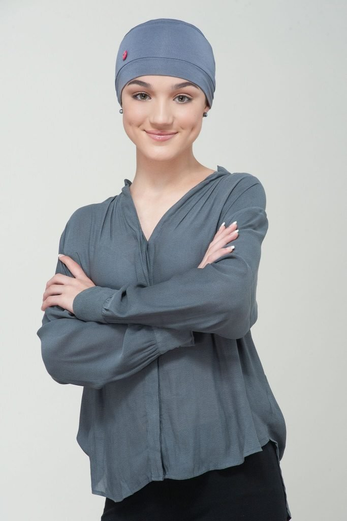 A girl wearing grey chemo cap with red button at the side