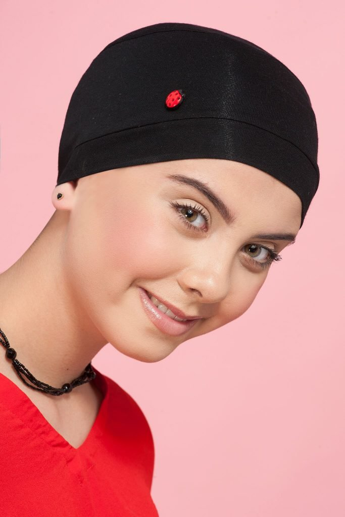 A girl wearing chemo cap with lady bug button at the side