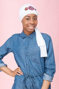 A teenage girl wearing white chemo cap with white and pink embellished scarf.