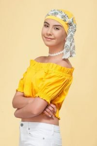 A teenage girl wearing yellow chemo hat for girls with fruit prints on the scarf