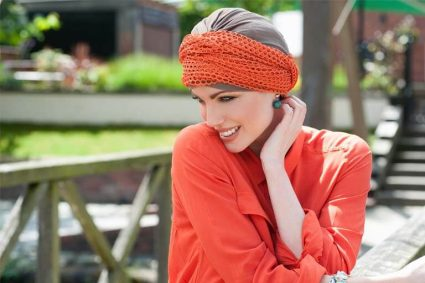 Woman wearing orange mesh scarf around a taupe chemo cap .