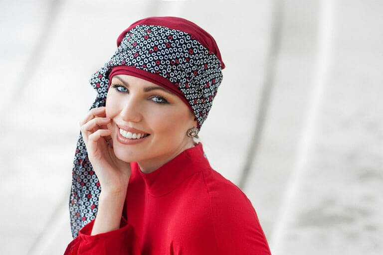 Woman wearing deep red chemo turban with attached circle printed scarf.