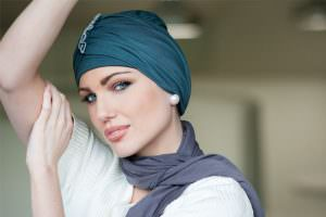 Hats for cancer patients UK Iris Woman wearing metallic grey headwear with ruffled detailing at the front.