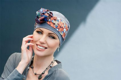 Headwear for people with cancer Yanna Grey Stone Allora Woman wearing grey chemo hat with geometric patterned scarf.