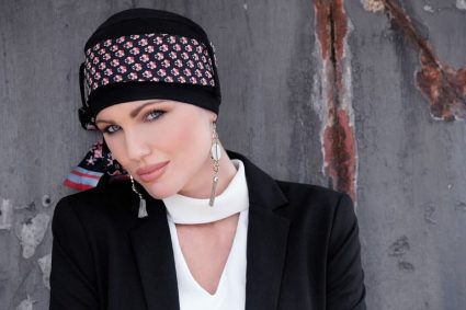 Woman wearing black chemo hat with delicate printed scarf