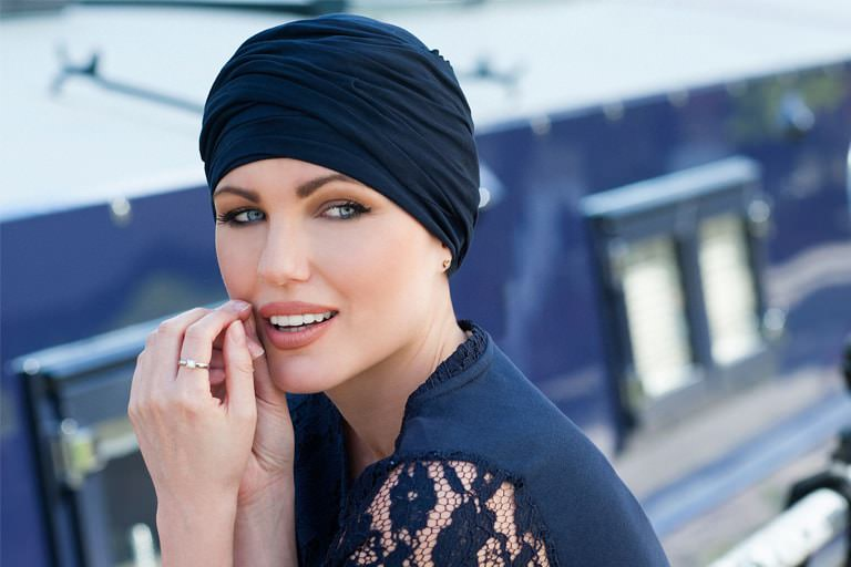 Woman wearing navy chemo headwear scarlet with delicate ruffle effect.