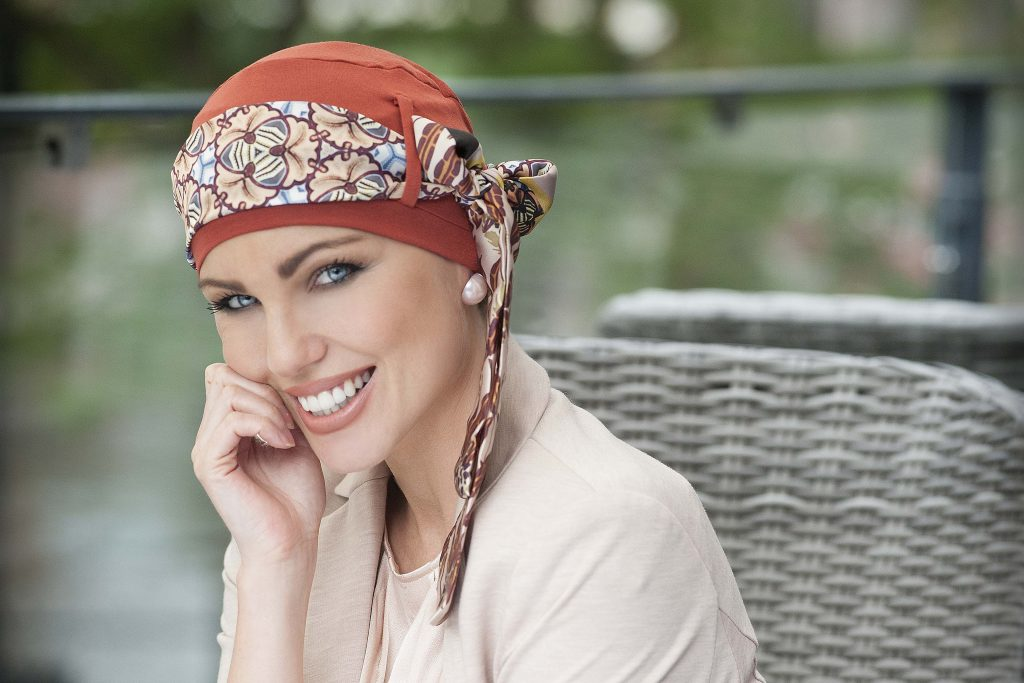 Woman in brick orange head cap with floral printed scarf