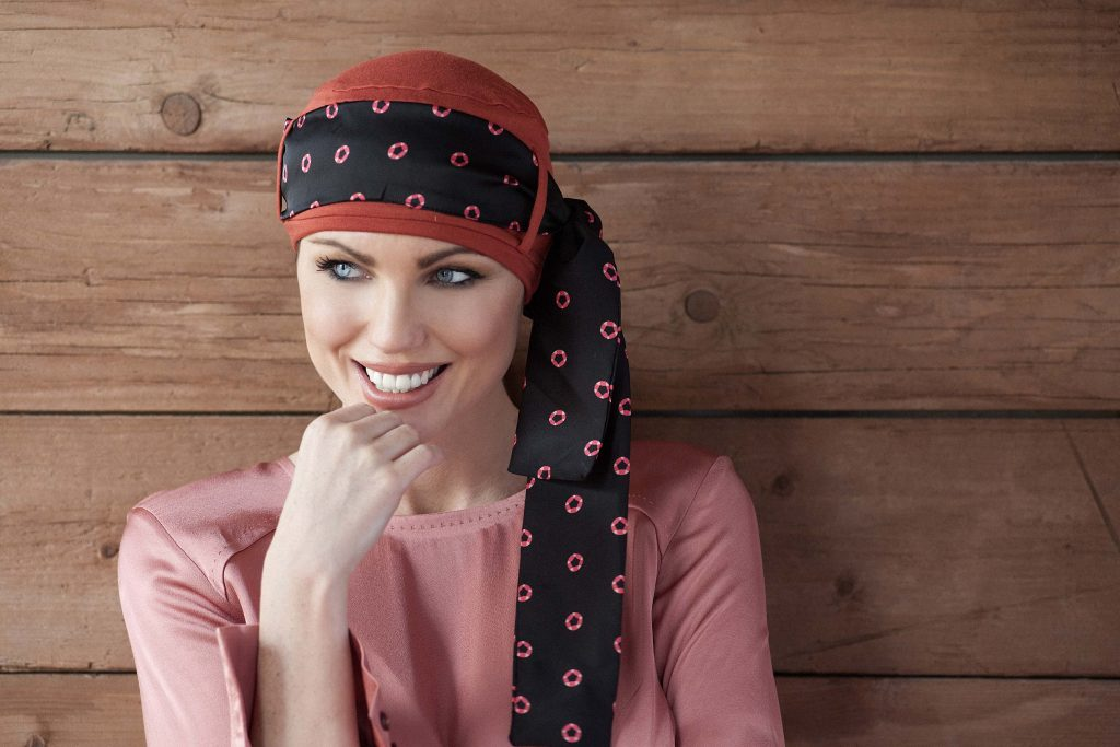 Chemo headwear for ladies Yanna Brick Diamond Rosabella Woman wearing brick orange head cap with diamond shaped prints on a black scarf