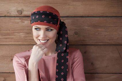 Chemo headwear for ladies Yanna Brick Diamond Rosabella Woman wearing brick orange head cap with diamond shaped prints on a black scarf