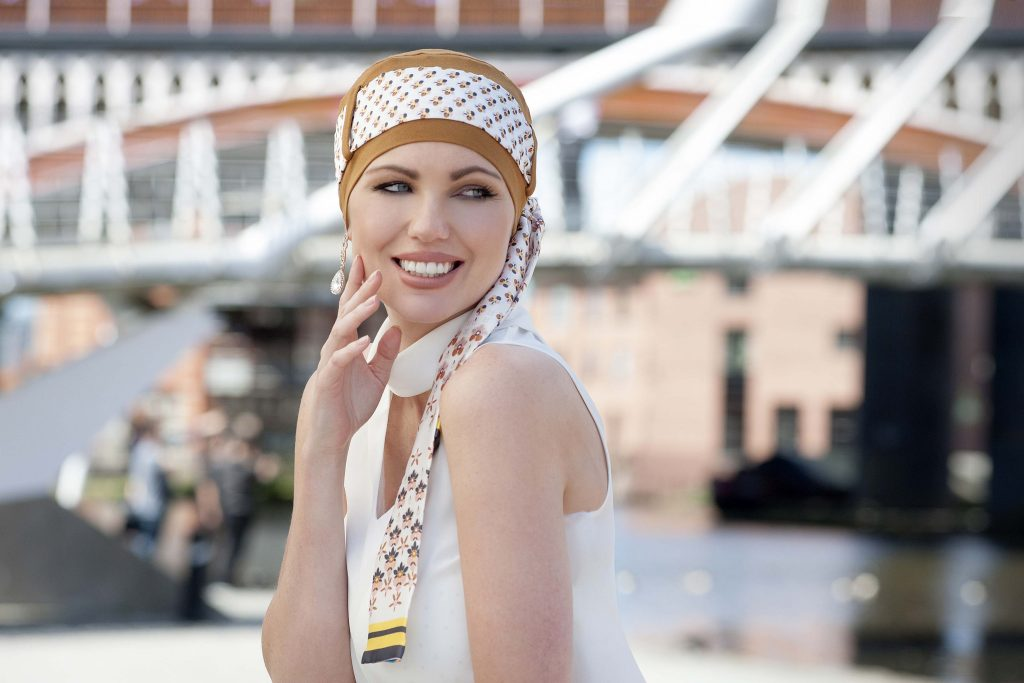 Woman in camel coloured head cap with floral patterned scarf around the head