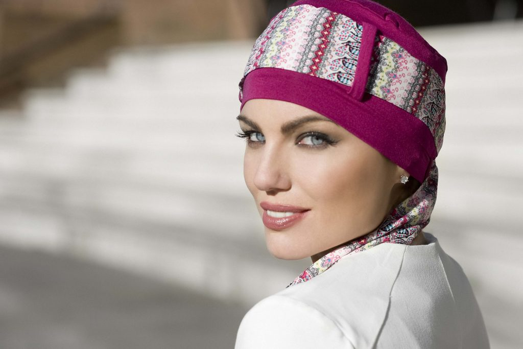 Woman wearing purple head cap with patterned scarf