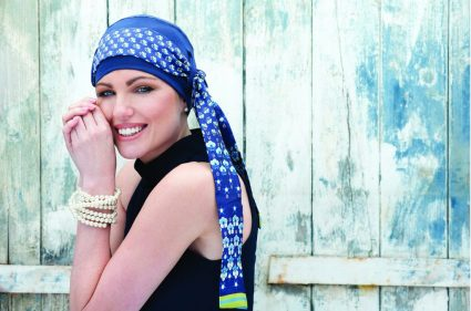 Woman wearing blue Bamboo chemo scarf with printed scarf.