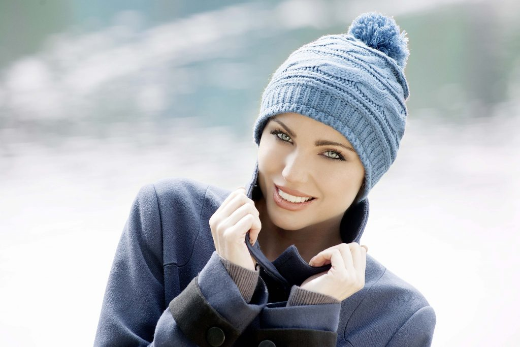Chemotherapy knitwear hat Ava Woman wearing a soft blue Single Rib Knit chemo beanie hat with pompom and soft fleece inside for extra comfort