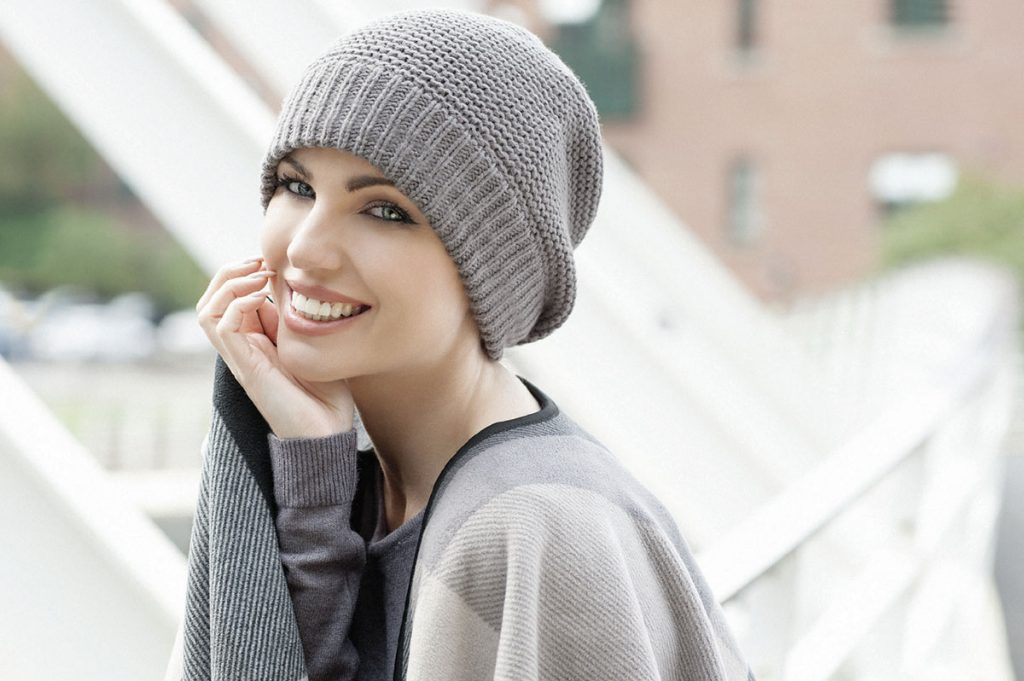 5c307761012 Woman wearing a soft grey knitted Basketweave Stitch chemo hat with soft  fleece inside for extra