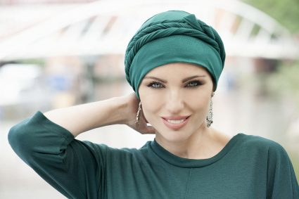 Woman wearing headwear for hair loss Asha soft cotton chemo cap with long tail which could be shaped in many ways