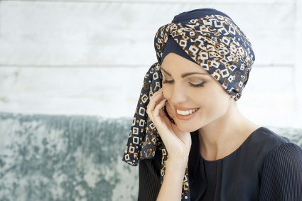 Woman wearing Navy soft cotton chemo hat with golden diamond scarf