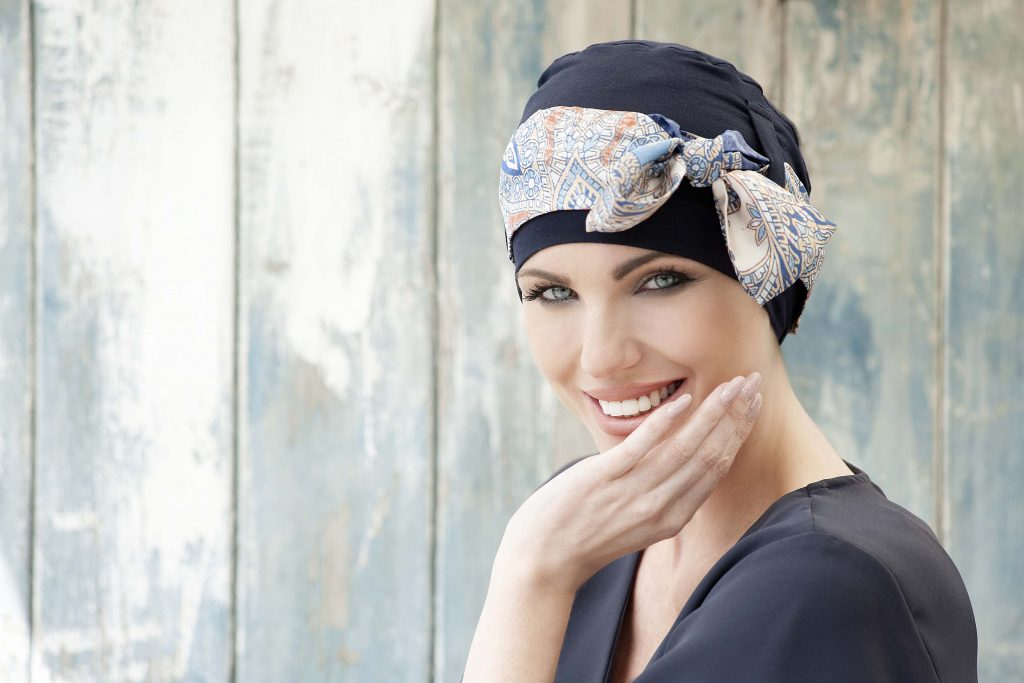Headwear for chemotherapy patients Yanna colour Navy Mosaica Linea Woman in navy colour bamboo chemo hat with mosaica patterned scarf around the headwear