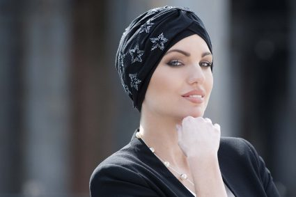 Woman wearing black embellished soft cotton chemo headwear with silver embroidery in the shape of star