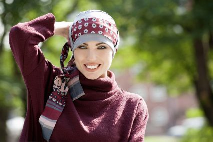 Woman in grey colour bamboo chemo hat with maroon floral patterned scarf around the headwear