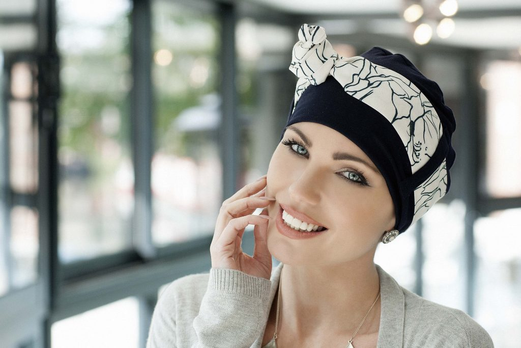 Head scarves for cancer patients UK Yanna Navy White Lilium Woman in navy colour bamboo hat with white patterned scarf around the headwear
