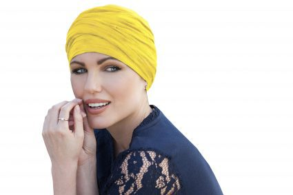 Woman wearing yellow sunshine chemo headwear scarlet with delicate ruffle effect.