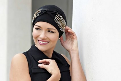 A woman wearing Carolina Black Laurel Crown – Headwear for Cancer Patients Women is the latest addition to Masumi Headwear's collection.