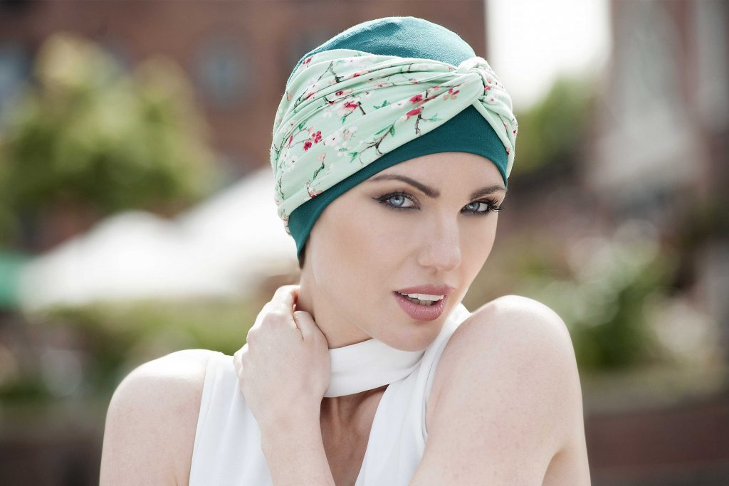 A woman wearing green chemo hat with a green headband called Ella Green Forest Flower-chemo hats for women
